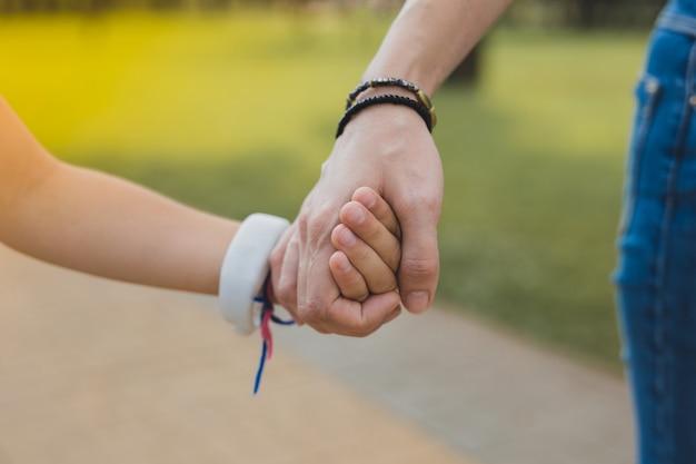 Schwarzes armband. liebevolle moderne mutter, die schwarzes armband trägt, das ihre tochter hält, die im park zusammen geht