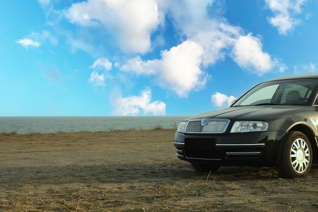 Schwarzes auto am hang gegen meer, platz für text