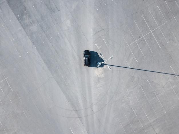 Schwarzes auto der spitze über ansicht, das auf leerem leerem asphalt läuft