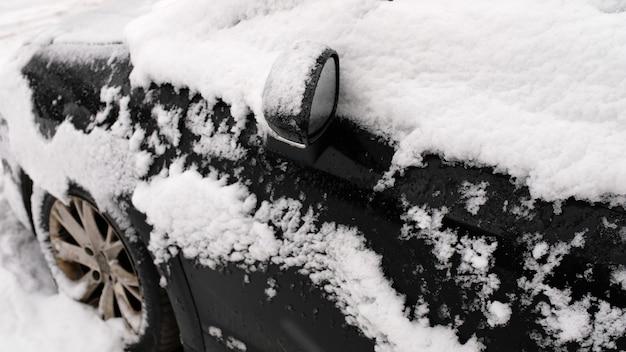Schwarzes auto im schnee auf dem parkplatz.
