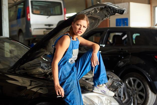 Schwarzes auto mit offener haube und weiblich-mechaniker auf ihm sitzt