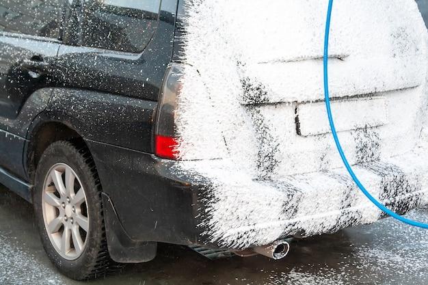 Schwarzes auto wird auf der selbstbedienungs-autowaschanlage mit schaum bedeckt. rückansicht des scheinwerfers und des kofferraums