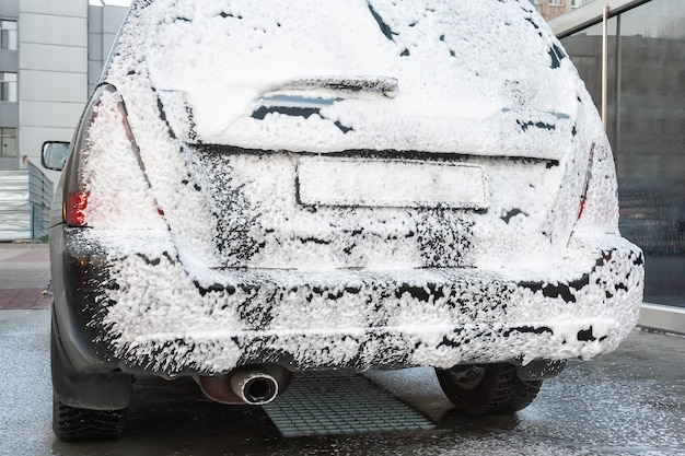 Schwarzes auto wird auf der selbstbedienungs-autowaschanlage mit schaum bedeckt. rückansicht