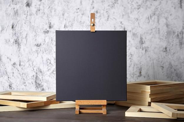 Schwarzes baumwoll-canvas auf einer hölzernen staffelei und keilrahmen auf dem tisch