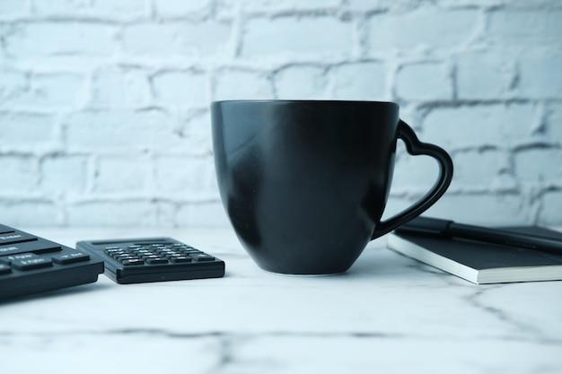 Schwarzes bechermodell mit mit tastatur, notizbücher auf tisch