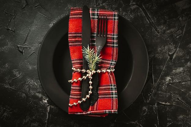 Schwarzes besteck auf roter serviette und schwarzem teller