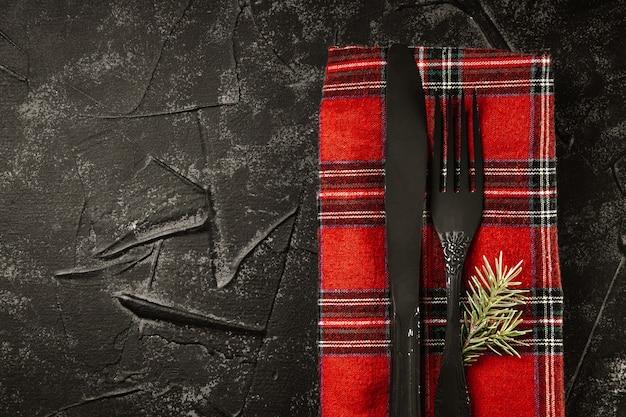 Schwarzes besteck auf roter serviette und tannenzweig