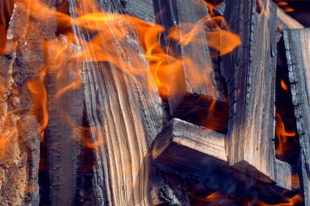 Schwarzes brennendes brennholz in flamme und asche. nahansicht