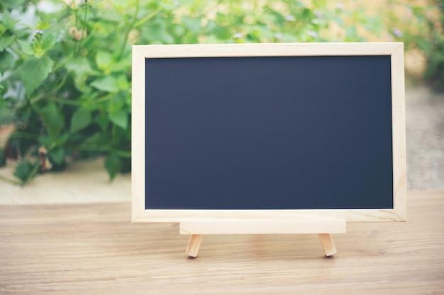 Schwarzes brett auf die hölzerne tischplatte mit grünem baum bokeh hintergrund der sonne und der unschärfe
