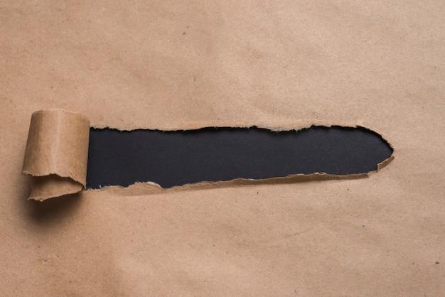 Schwarzes brett, das durch kraftpapier schaut