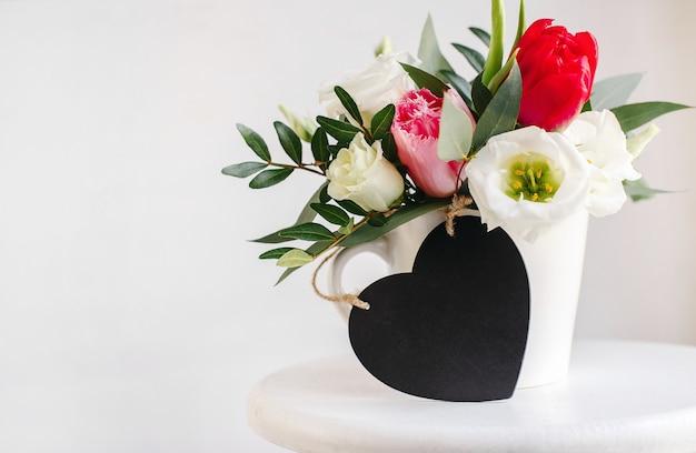 Schwarzes brett herz exemplar. frühlingsblumenstrauß in weißer vase auf weißem holzständer. rosen, tulpen und lisianthus.
