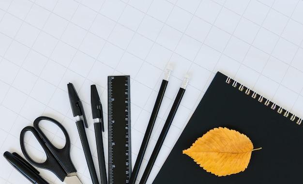 Schwarzes briefpapier, herbsturlaub auf weißem kariertem papier