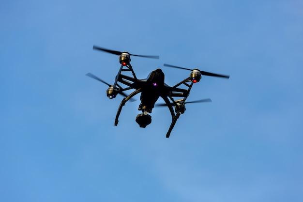 Schwarzes brummen quadcopter mit der kamera, die über blauen himmel fliegt. winkelansicht