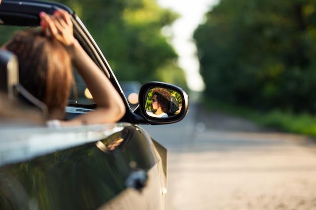 Schwarzes cabriolet auf der straße an einem sonnigen tag. im seitenspiegel spiegelt sich der dunkelhaarige junge mann mit bart. .