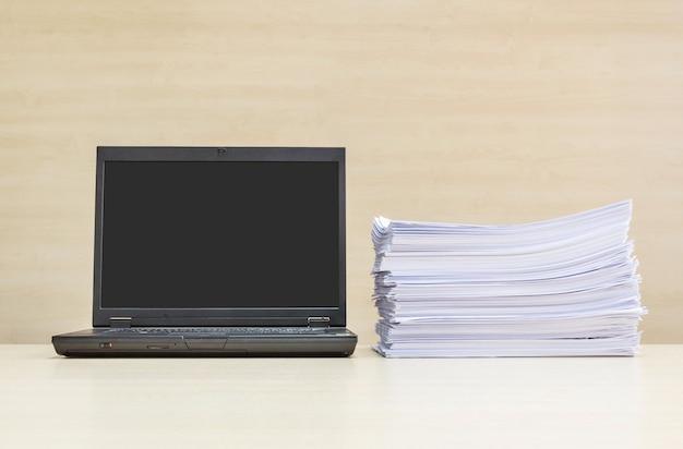 Schwarzes computernotizbuch der nahaufnahme und stapel des arbeitspapiers auf unscharfem hölzernem schreibtisch und hölzerner wand im konferenzzimmer masern hintergrund