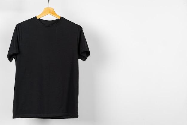 Schwarzes einfaches t-shirt, das an einem kleiderbügel hängt, kopieren raum