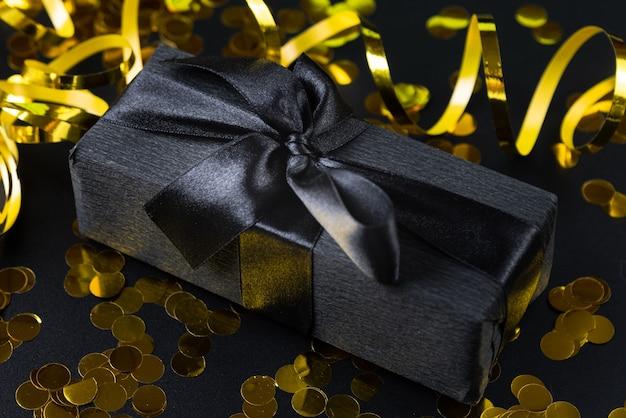 Schwarzes eingewickeltes geschenk mit konfetti