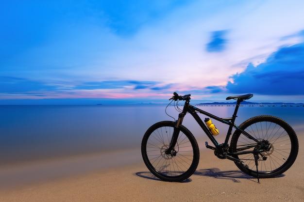 Schwarzes fahrrad auf dem strand bei sonnenuntergang in pattaya, thailand