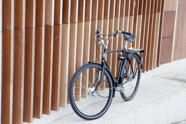 Schwarzes fahrrad auf einer modernen wand unterstützt