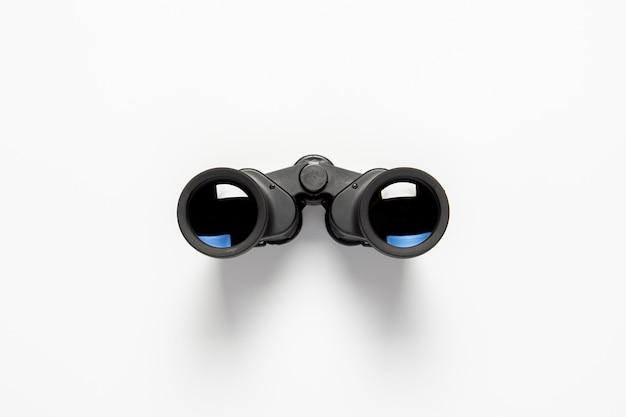 Schwarzes fernglas auf weißem hintergrund. flache lage, draufsicht