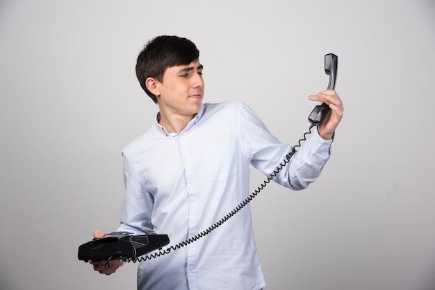 Schwarzes festnetztelefon in der hand eines mannes auf grauer wand.