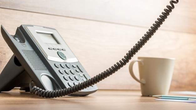 Schwarzes festnetztelefon mit abgenommenem hörer und außerhalb der foto- und kaffeetasse daneben auf dem schreibtisch aus holz.