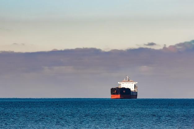 Schwarzes frachtschiff, das in stillem ostseewasser bewegt. riga, europa