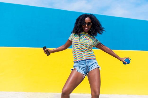 Schwarzes frauenporträt der gemischten rasse lächelnd mit großen afro-lockigen haaren gegen blauen und gelben wandtanz beim halten eines smartphones