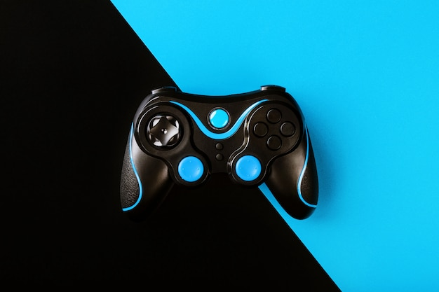 Schwarzes gamepad auf schwarzer und blauer oberfläche
