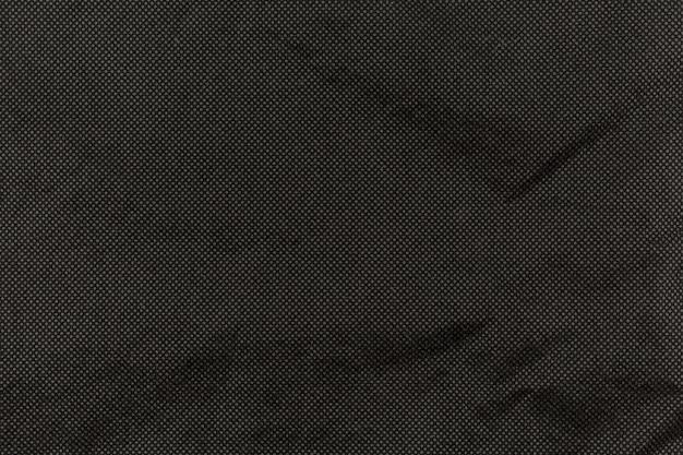 Schwarzes gefaltetes papier mit rauem texturhintergrund