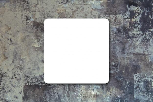 Schwarzes gefaltetes weißbuchplakat, das an der schwarzen steinwand, schablonenspott für das addieren ihres textes hängt.