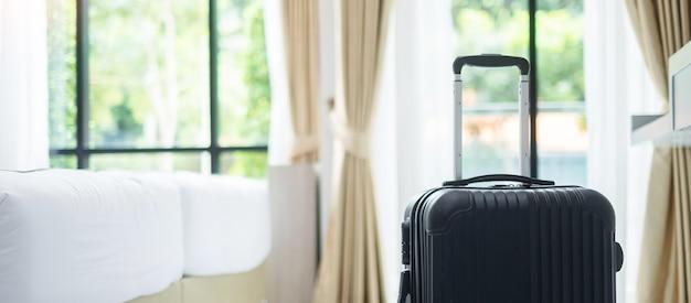 Schwarzes gepäck im modernen hotelzimmer mit fenstern. zeit zu reisen, entspannung, reise, reise und urlaubskonzepte