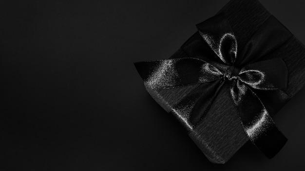 Schwarzes geschenk auf dunklem hintergrund
