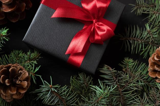 Schwarzes geschenk in schwarzem papier eingewickelt mit einem roten band und einer schleife mit zweigen eines weihnachtsbaumes