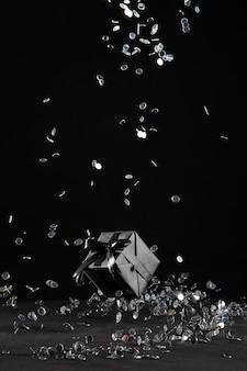 Schwarzes geschenk mit konfetti-anordnung