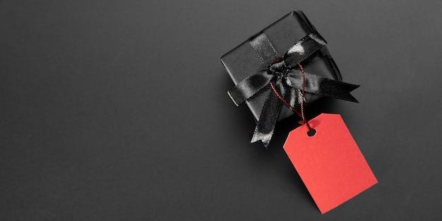Schwarzes geschenk mit rotem etikett