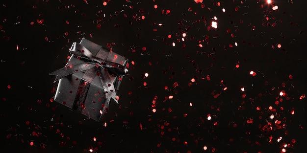 Schwarzes geschenk mit rotem glitzer auf schwarzem hintergrund