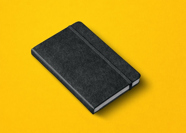 Schwarzes geschlossenes notebook-modell isoliert auf gelb