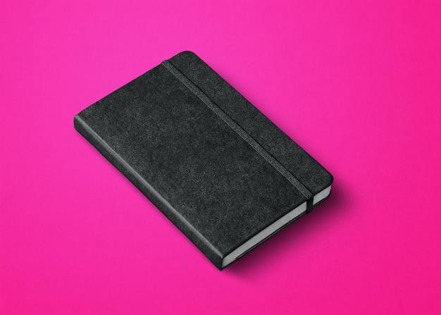 Schwarzes geschlossenes notizbuchmodell isoliert auf rosa