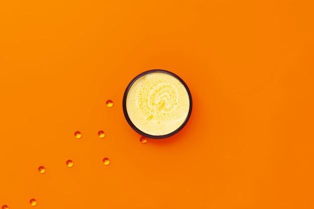 Schwarzes glas mit gelber creme mit sanddornöl, daneben kapseln mit vitamin e.