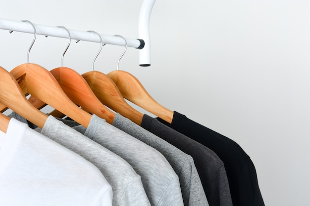 Schwarzes, graues und weißes farbt-shirt, das am hölzernen kleiderbügel hängt