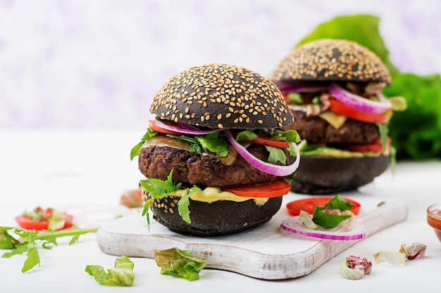 Schwarzes großes sandwich - schwarzer hamburger mit saftigem rindfleischburger, käse, tomate und roten zwiebeln auf heller oberfläche.