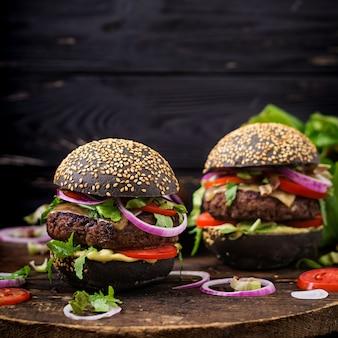 Schwarzes großes sandwich - schwarzer hamburger mit saftigem rindfleischburger, käse, tomate und roten zwiebeln auf schwarzer oberfläche