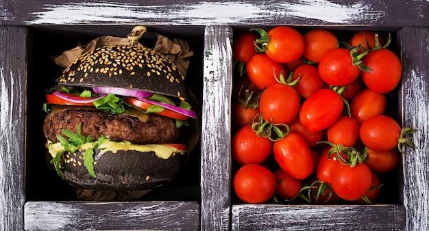 Schwarzes großes sandwich - schwarzer hamburger mit saftigem rindfleischburger, käse, tomate und roten zwiebeln in der schachtel auf schwarzer oberfläche. flach liegen. draufsicht
