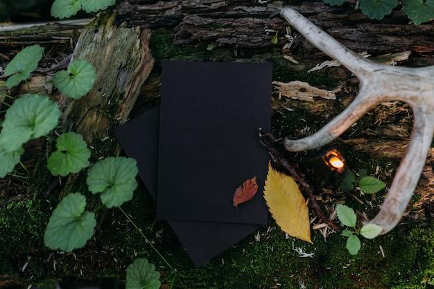 Schwarzes handwerkspapiermodell schwarze kerze auf dem hintergrund der magischen natur des waldes
