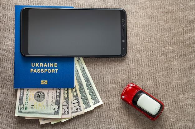 Schwarzes handy, geld us-dollar banknoten rechnungen, reisepass und spielzeugauto
