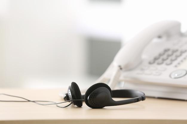 Schwarzes headset auf dem tisch des mitarbeiters des technischen supports im büro