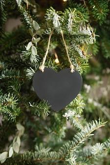 Schwarzes herz aus holz auf grünem hintergrund von tannenzweigen. zusammensetzung weihnachten neujahr. moke up, kopieren sie platz für den valentinstag.