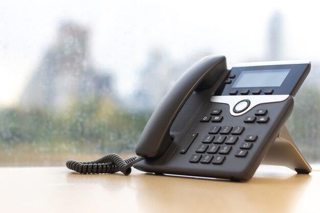 Schwarzes ip-telefon auf holztisch, telefon auf schreibtisch mit großer fensterstadtansicht modernes bürokonzept.