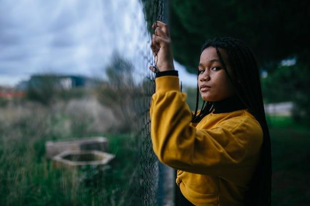Schwarzes junges mädchen, das sich an einem zaun festhält, mit dramatischem und traurigem ausdruck